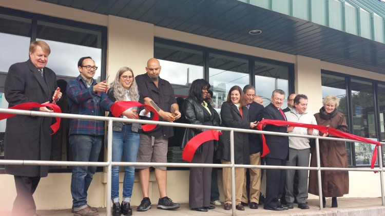Rich Fitzgerald, Michael and Alyssa Studebaker, John Fetterman and other state and local officials cut the ribbon for the Free Press building renovation project. Photo by Kim Lyons.