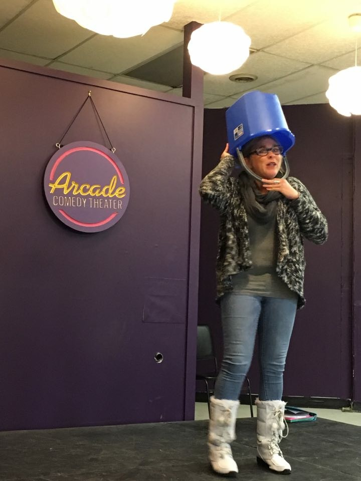 Bethany Ruhe with a bucket on her head. Yep. At the Arcade Comedy Theater.