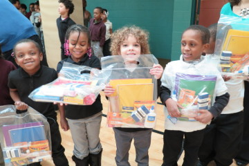 Students receiving school supply kits from The Education Partnership