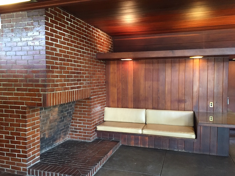 The interior shows the influence of Frank Lloyd Wright with its built-in seating and strong horizontal lines.