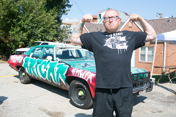 Jason Sauer - Most wanted fine art- stands in front of his art car