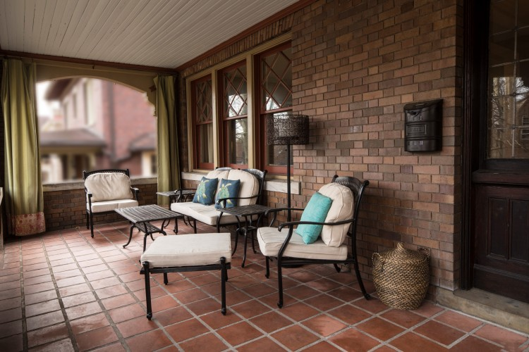Spacious, tiled front porch with flowing draperies and original wood-slatted ceiling.