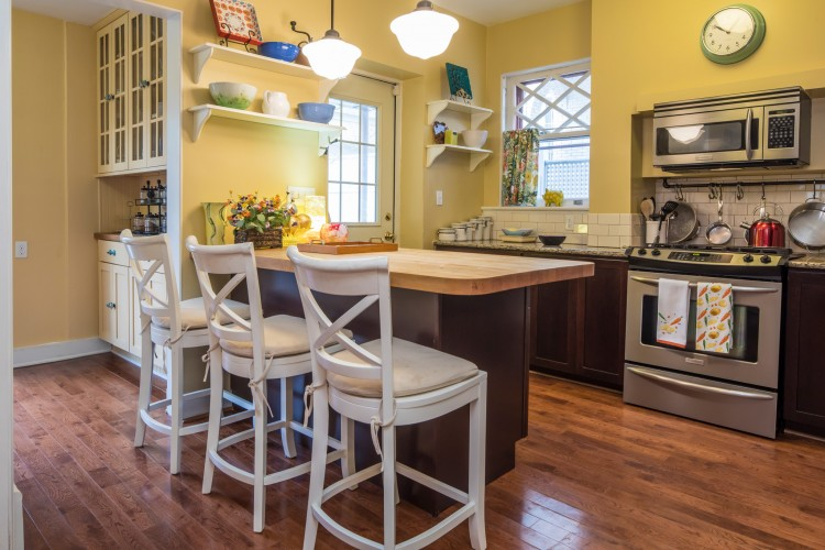 Eat-in kitchen with stainless-steel appliances, including gas stove top. It boasts a butcher block and granite counter top, with handsome cherry wood cabinets.