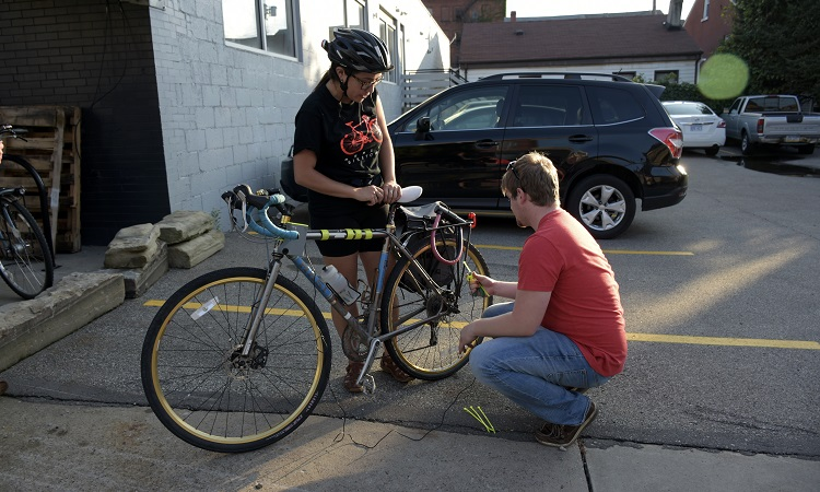 2016 PGH Lab cohort TransitSource attaches a Sentinal Box to a volunteer's bike. Image courtesy of PGH Lab.