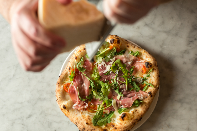 Prosciutto & Arugula pie at Pizzuvio. Photo by: Matt Dayak