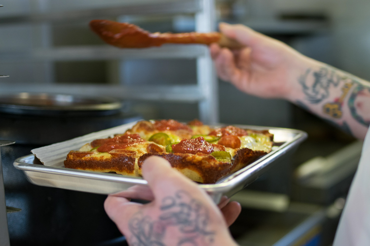 """Prepping the """"Detroit-style"""" pizzas at Michigan & Trumbull's recent pop-up event. Photo by Christopher White."""